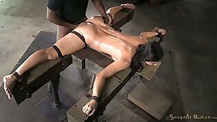 Doing the splits oiled tied up brunette has to suck two dicks